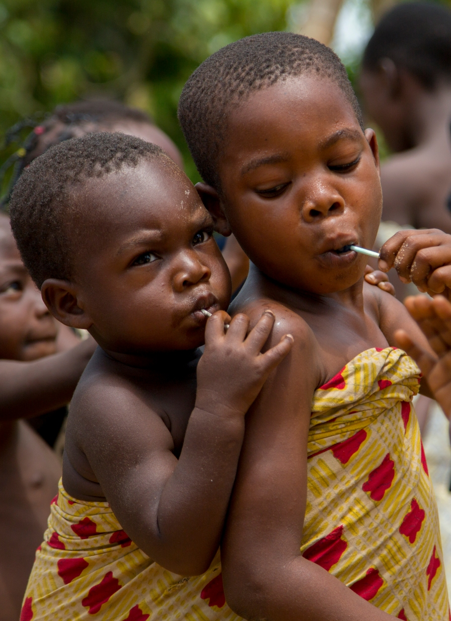 Siblings share a lollipop after a church service in a rural Ghana village.