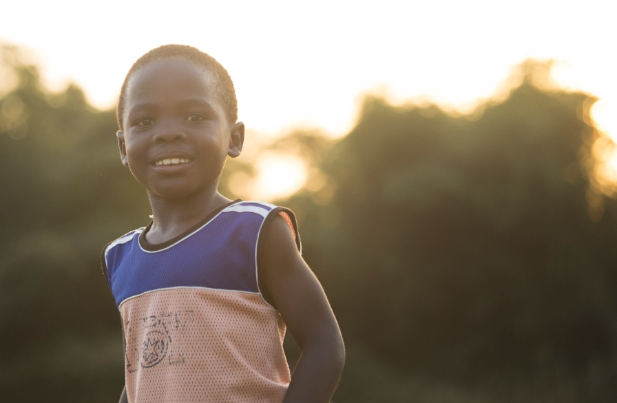 A young boy playing soccer at sunset.