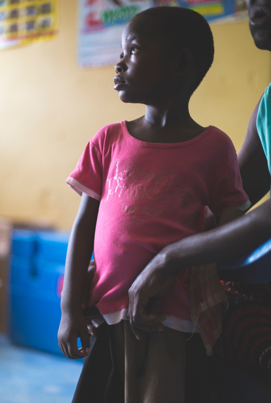 A young girl waiting to be seen by a doctor at a medical clinic in Ghana.