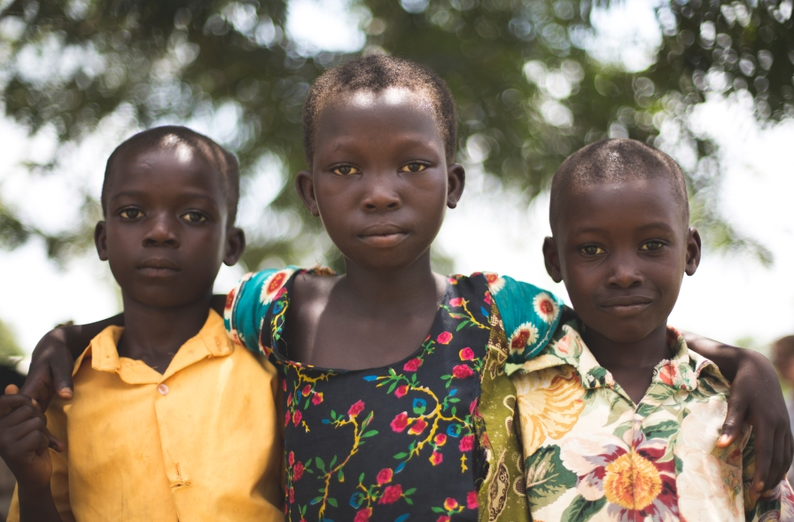 A group of friends pose for a photo outside a medical clinic n Ghana.