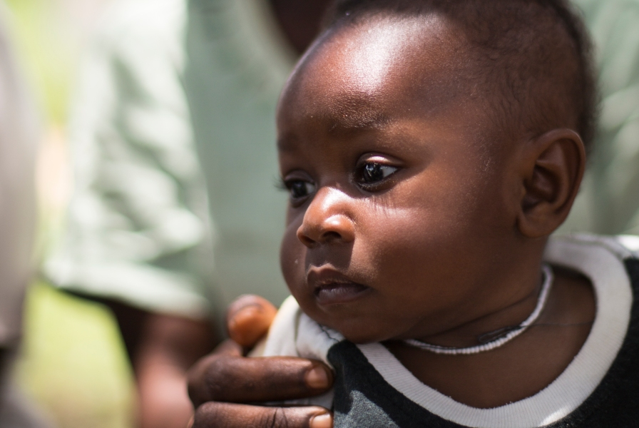 A child sitting on his mother's lap outside a medical clinic in Ghana.