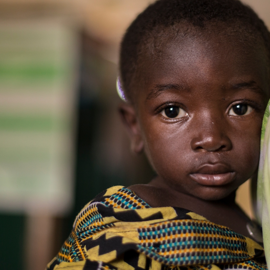 A child sits on his mother's back while waiting for medication at a medical clinic in Ghana.