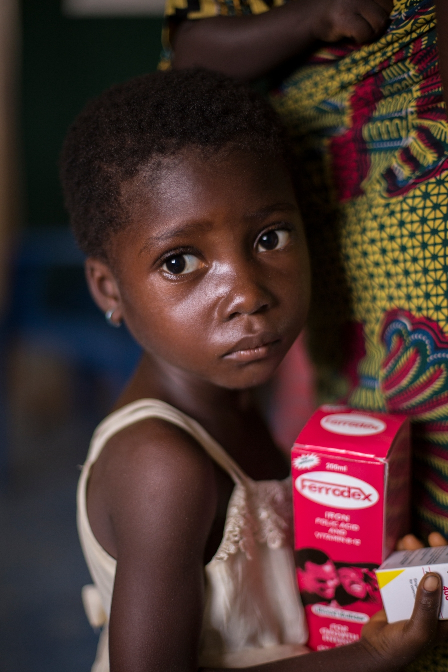 A child waits next to her mother while waiting for medication at a medical clinic in Ghana.