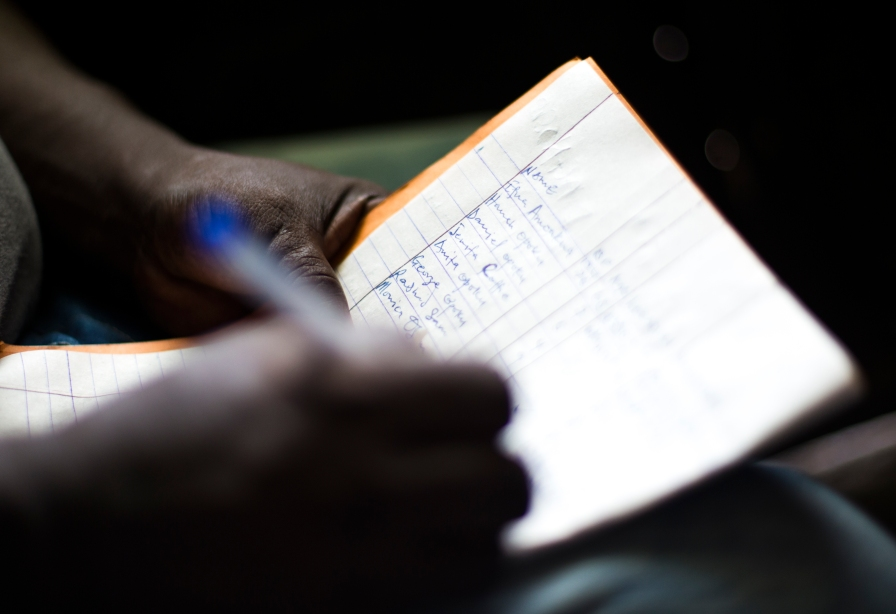 A man writes down a patient's vital signs at a medical clinic in Ghana.
